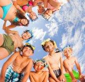 Fotografie Zvláštní skupina dětí v plavky a šnorchlování maskami, sklonil se nad pohledu na fotoaparát shora na pozadí modré oblohy