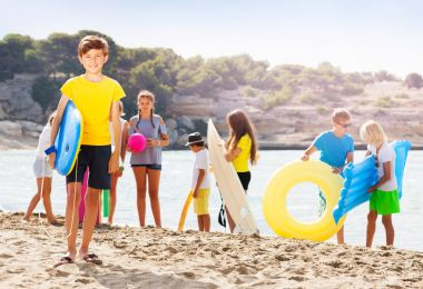 Boy stand on the sand beach with group of friends on background holding swimming boards and inflatable toys