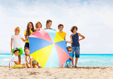 Boys and girls sit with beach umbrella in a large group of fiends on hot summer day near the sea on sand