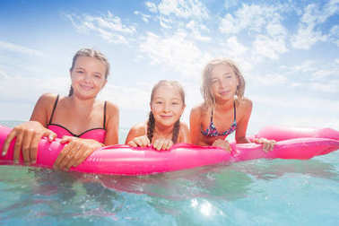 Group of three girls swim on the pink matrass in the sea in swimming suits happy and smiling
