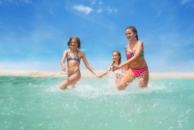 Three best friends girls in swimsuits running in shallow water while making fun splashes