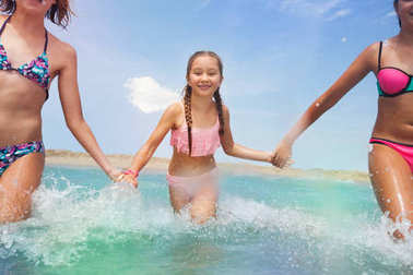Three girls holding hands run into the sea together smiling in swim suits
