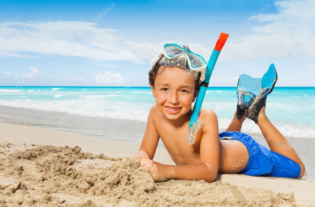 Happy smiling boy laying on the tropical beach in scuba mask and flippers with smile