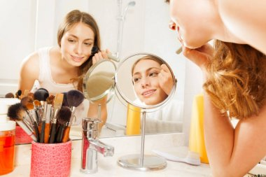 Portrait of attractive young woman applying daily makeup using brush, seen in bathroom mirror