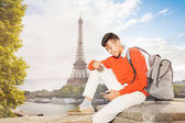 Happy teenage African boy sitting on the embankment of Seine river with the Eiffel Tower on background and texting on smart phone