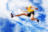 Sportsman remains in air while jumping against cloudy sky