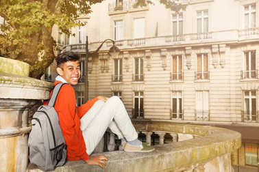 Happy African student with backpack sitting on the street of Paris