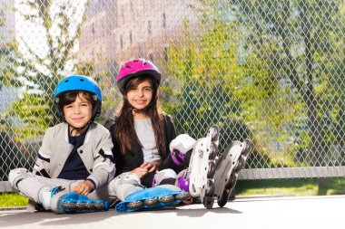Happy preteen boy and girl in roller skates, sitting on the floor outdoors at sunny day