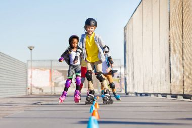 Preteen boys and girls, happy inline skaters, rolling at skate park in summer