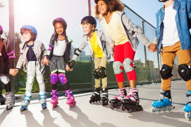 Group of multiethnic children, happy in-line skaters in protective gear, standing in a row holding hands outdoors at sunny day
