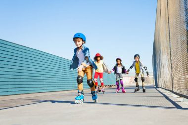 Happy preteen boy playing roller skates with friends outdoors at stadium