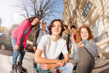 Multiethnic children with inline skates and skateboards posing together at city street