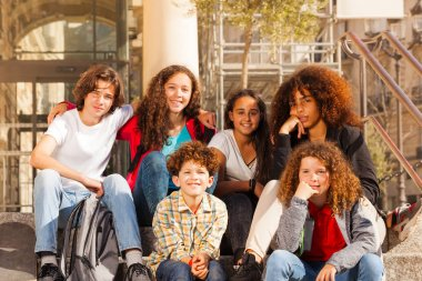 Big group of multiethnic teenage boys and girls sitting together outdoors on staircase at sunny day