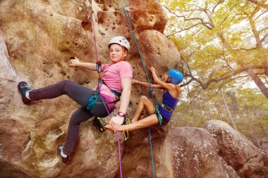 Young girls in helmets climbing a rock in forest area