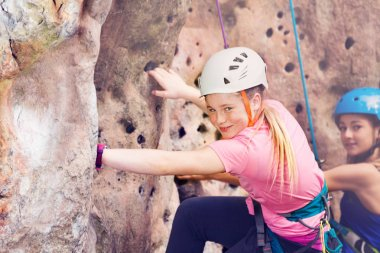 Close-up portrait of teenage girl, happy rock climber in helmet training outdoors