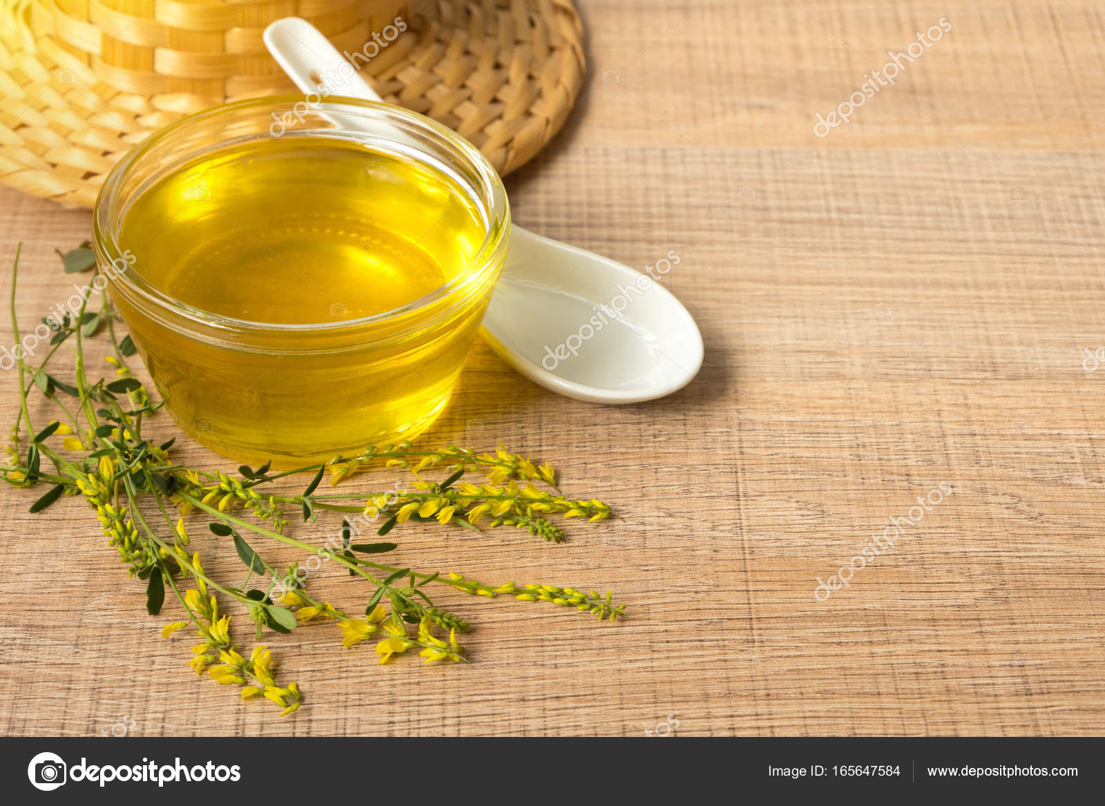 Glass Cup With Honey And Wild Flowers With A Yellow Clover On A