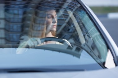 young adult blonde woman driving a car