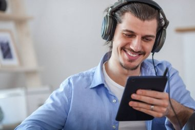 Handsome happy man looking to the dark blue tablet