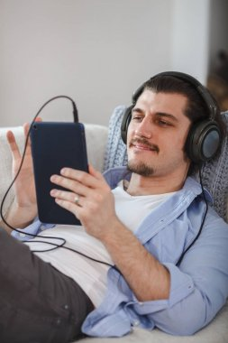 Handsome guy lying on sofa with tablet and headphones