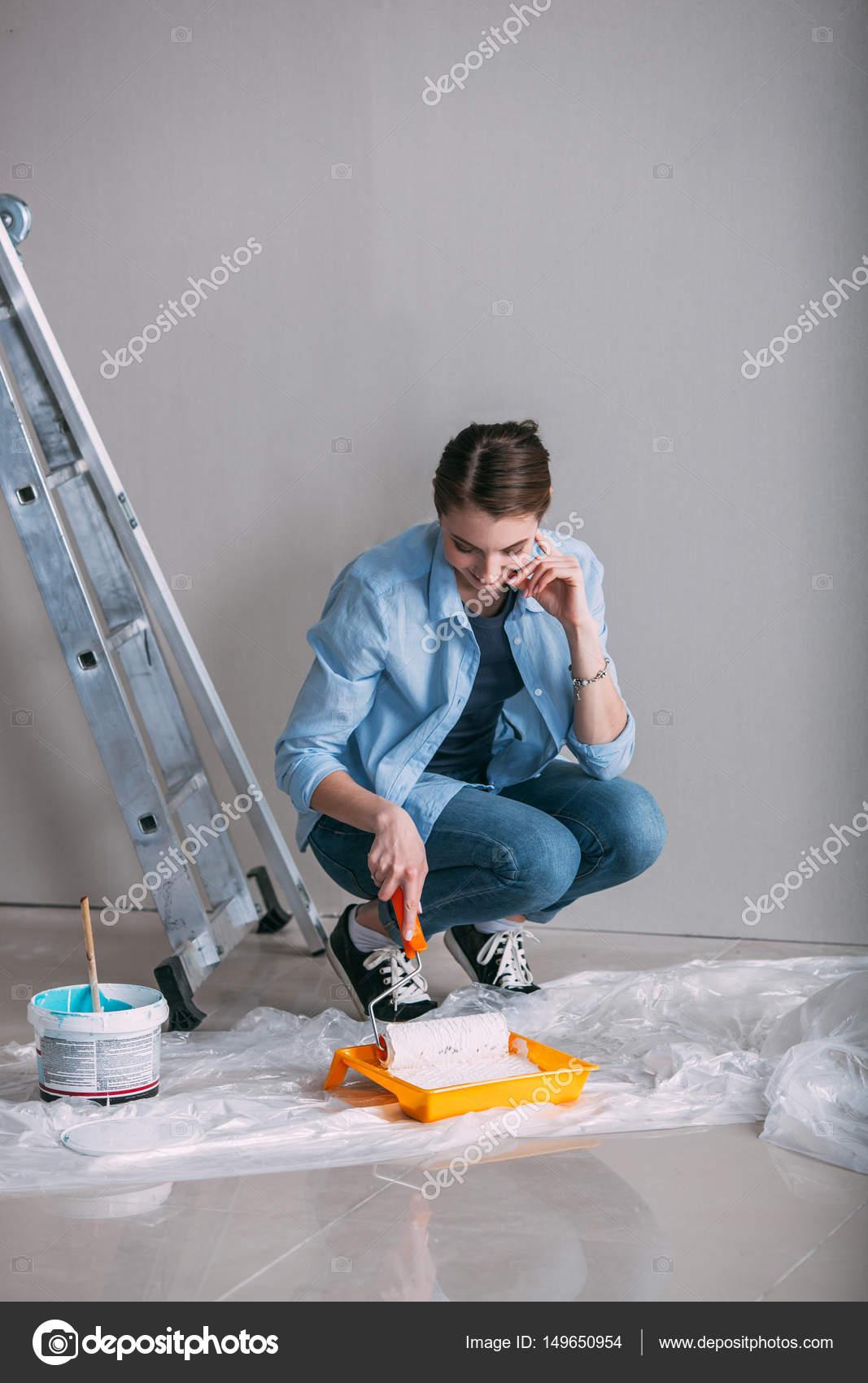 Donna che si siede sulla vernice pavimento e disegna sul for Disegna i piani domestici online