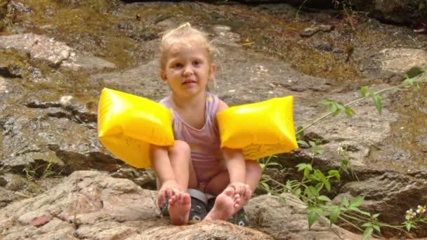 dívka v žluté rameno ruce sedí na kameni