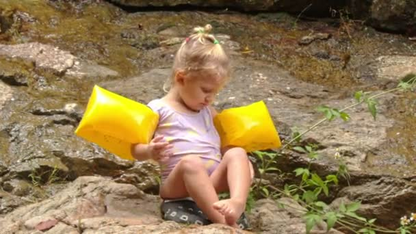 girl in yellow arm-hands sits on stone