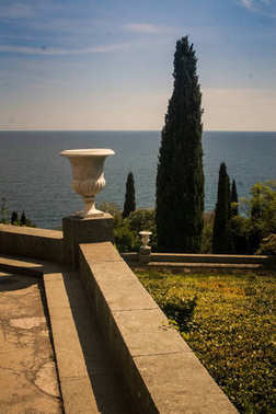 Crimea Vorontsov palace park with marble vase and cypress against azure sea in springtime