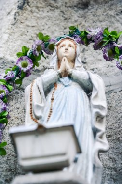 closeup marble sculpture of praying woman against stone and violet flowers garland