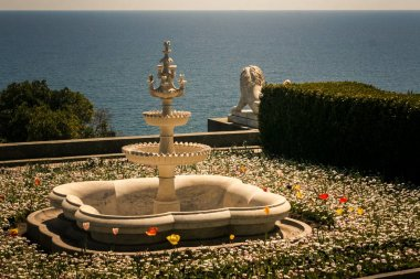 three level fountain among flowers in park of Vorontsov palace against azure sea in Crimea Ukraine in spring