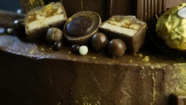 Nahaufnahme-Panorama auf Schokoladenkuchen mit Bonbons verziert und mit Lebensmittelgold bestreut