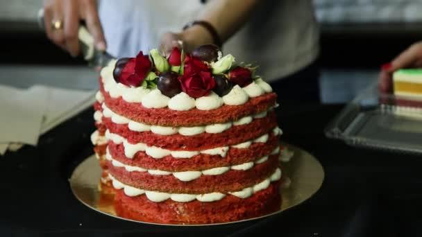 cukrász kezét lassan vágott részre piros házi készítésű süteményeket díszített fehér bizet, a szőlőt és a vörös és a fehér rózsák