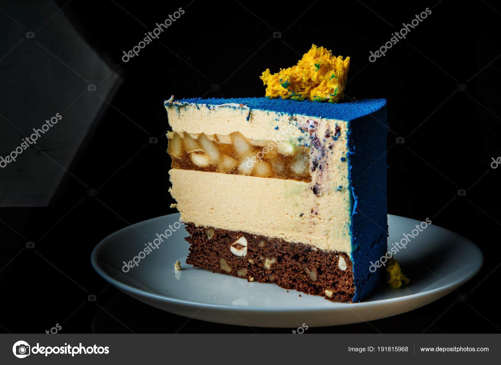 Pezzo di torta mousse blu con decorazione di torta di spugna gialla sul  Inter,livello top e caramello pera si trova sulla zolla bianca su sfondo  nero\u2013