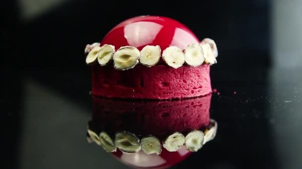 Vergrößern auf rotem Mousse-Dessert, das mit getrockneten Bananen dekoriert und mit roter Glasur auf spiegelschwarzem Hintergrund überzogen ist