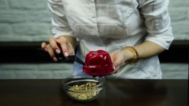 cukrář zdobí červené zasklené pěna dezert na pečiva s čokoládou plnění s drcenými ořechy