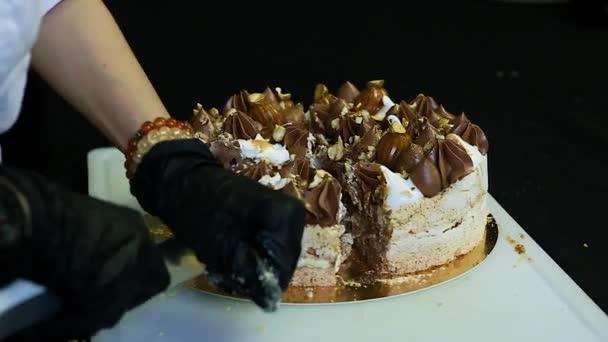 cukrář ruce snížit o nůž dvouvrstvé Kyjev dort bohatě zdobené čokoládovou smetanou a ořechy na bílém pozadí