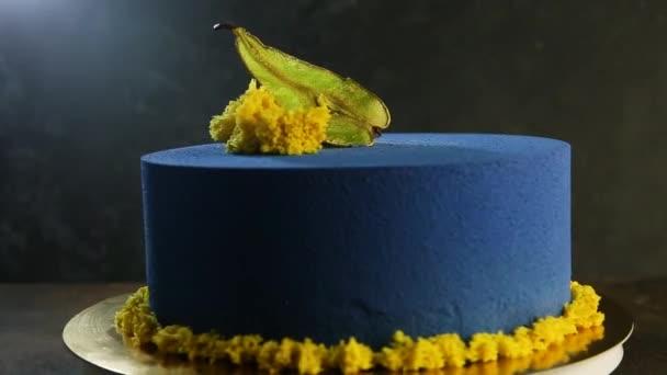 krásný modrý kulatý dort zdobený sušené hrušky a kousky žlutého piškotový dort porostů na tmavém pozadí