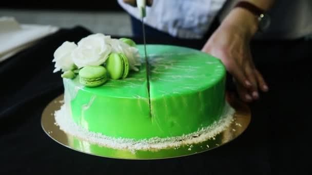 cukrář ruce kácet zasklené zelené musse dort zdobený bílými květy, kokosové chipsy a makronky ve dvou částech