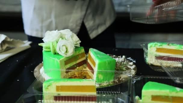 cukrář ruce kácet musse prosklené zelené musse dort zdobený bílými květy, kokosové chipsy a makronky na malé kousky