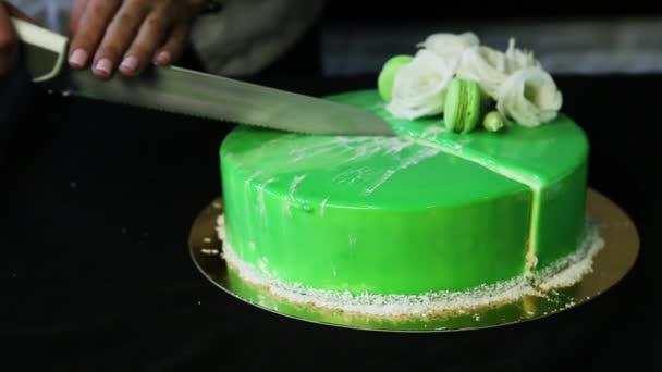 cukrář ruce kácet zasklené zelené musse dort zdobený bílými květy, kokosové chipsy a makronky na malé kousky