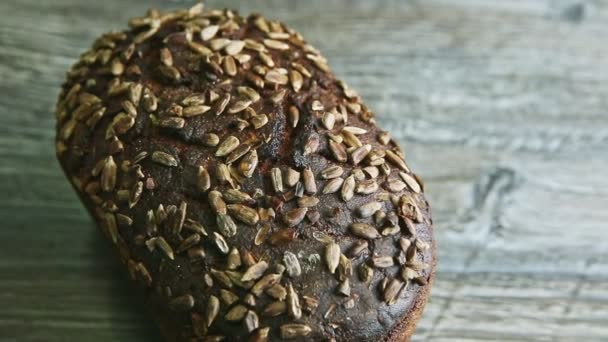 top view zoom out from whole tasty handmade rectangular rye bread with sunflower seeds on dark wooden table
