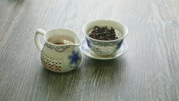 hagyományos fehér porcelán teáskanna tealevéllel és vízforraló forró teával