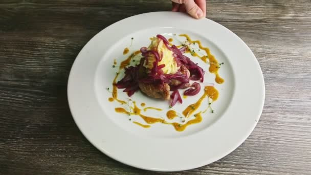 lidská ruka otáčí talířem se smaženými kousky masa s bramborovou kaší