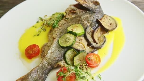 zoom ki az egész sült hal és zöldség pörgő körül