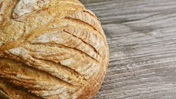 Nahaufnahme-Panorama eines ganzen runden Brotlaibs auf einem Holztisch