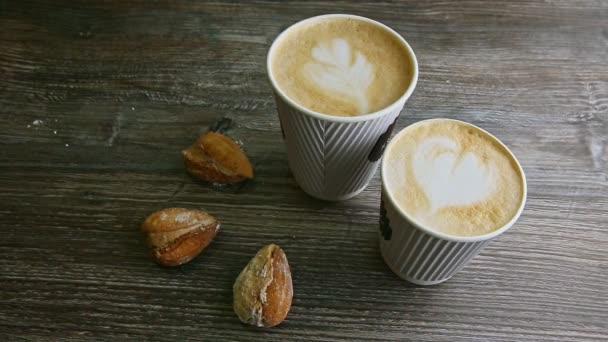 top view of two cups of milk coffee and three homemade almond shape cookies served on dark wooden table background