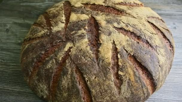 zoom out from big whole homemade round black rye bread with interesting texture surface on dark wooden table