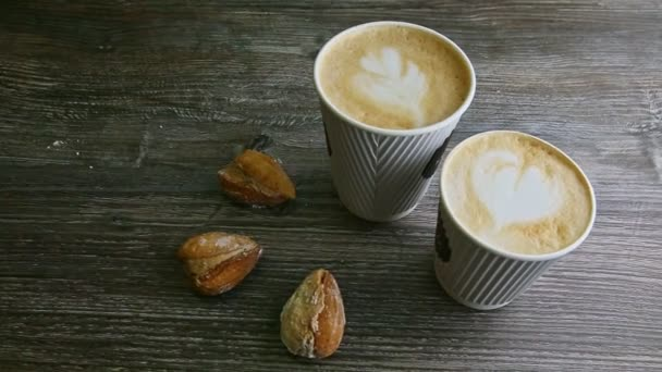 zoom in at two cups of milk coffee and three homemade almond shape cookies served on dark wooden table background
