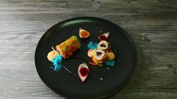 panorama v exkluzivních zdobených zeleninových rolích plněných mletým masem podávaným s různými omáčkami v cibulových plátcích na černém talíři na dřevěném stole