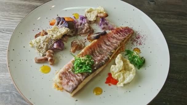 pomalé přiblížení na původně zdobené rybí filety se zeleninou se otáčí na talíři