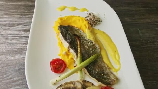 vynikající pečené filet z mořských ryb na bramborové předení a plátky zeleniny rotuje na talíři